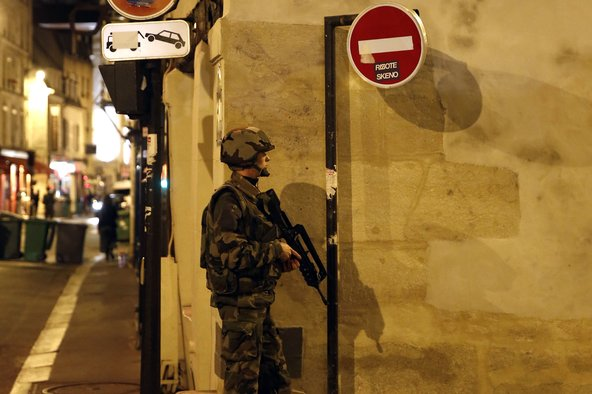 A soldier helping secure the area near La Belle Equipe, on Rue de Charonne, at the site of an attack in Paris.